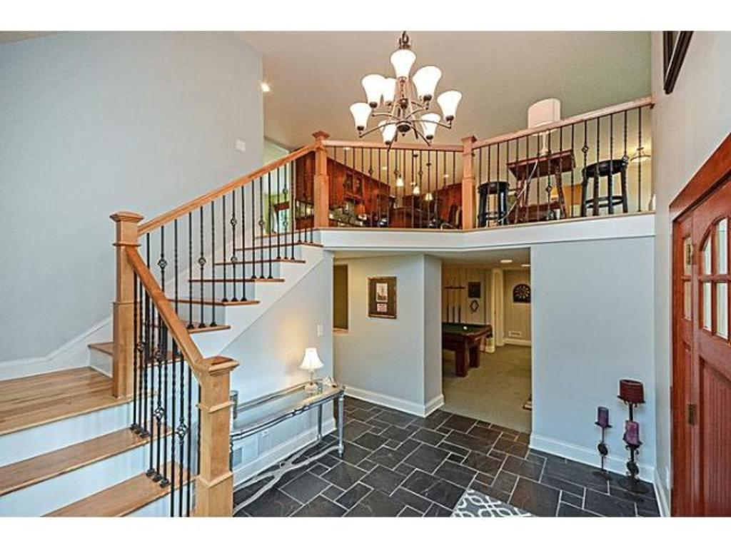 Walk through the door to an impressive, open foyer. This is a shot which features the staircase going up to the main level great room concept space!