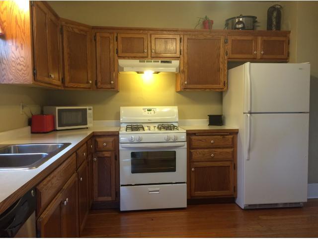 Natural light fills this kitchen with original hardwood flooring.