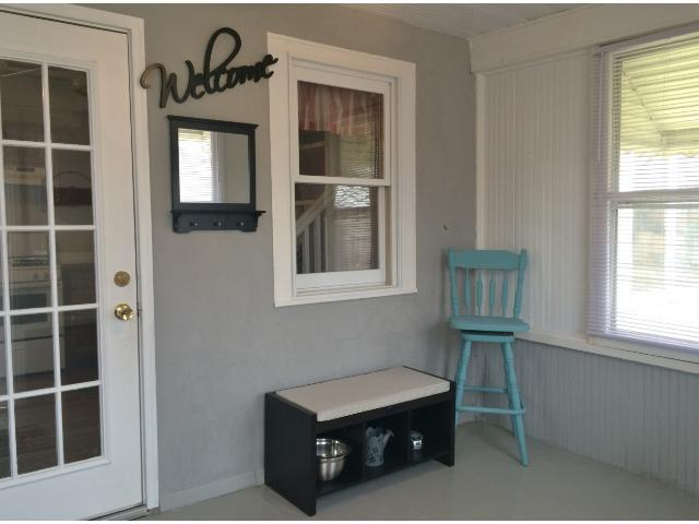 Step into the porch from the back yard.  Keep the family organized with plenty of space to hang outerwear and kick off your boots. Wainscoting and fresh paint add to the charm.