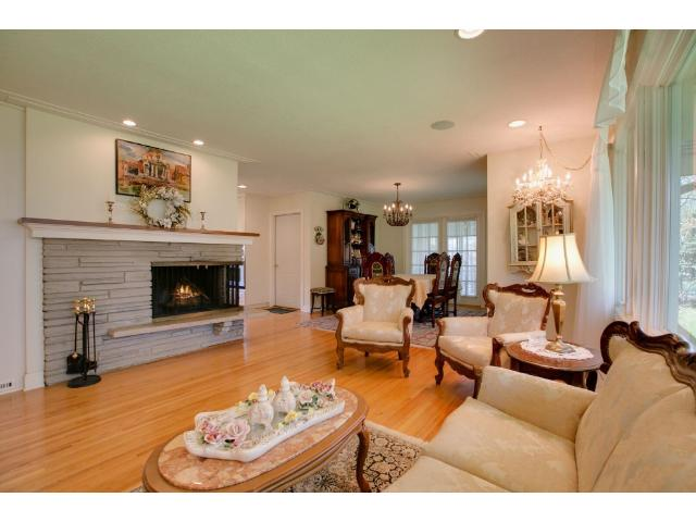 Gleaming hardwoods on main floor with cozy fireplace, formal dining room, and three season screened in porch for unwinding and relaxing.