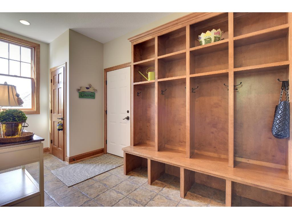 The large mudroom has 4 cubbies, closet, tile floor, access to the 3 car heated attached garage and has an adjacent powder room