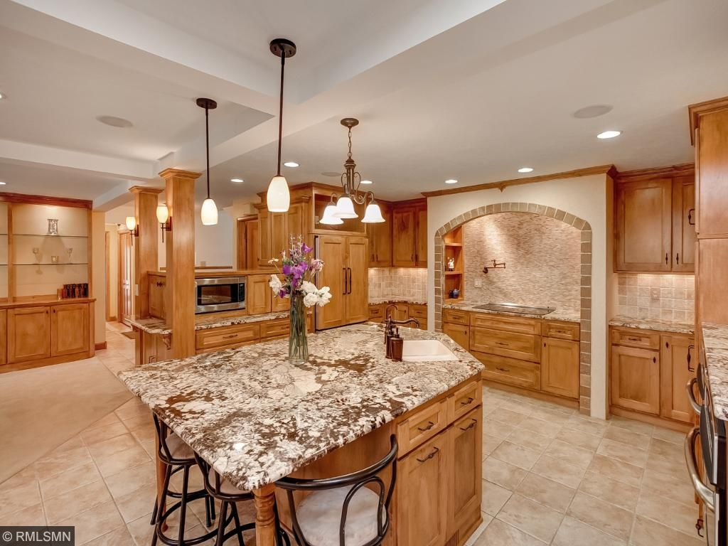 Over Sized Granite Center Island That Is A Breakfast Bar It Includes A Sink.